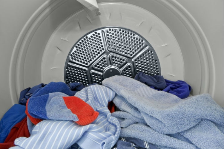 Toss wrinkled clothes in the dryer with a wet towel.