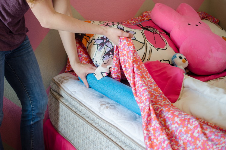 Prevent kids from falling out of bed with a pool noodle.