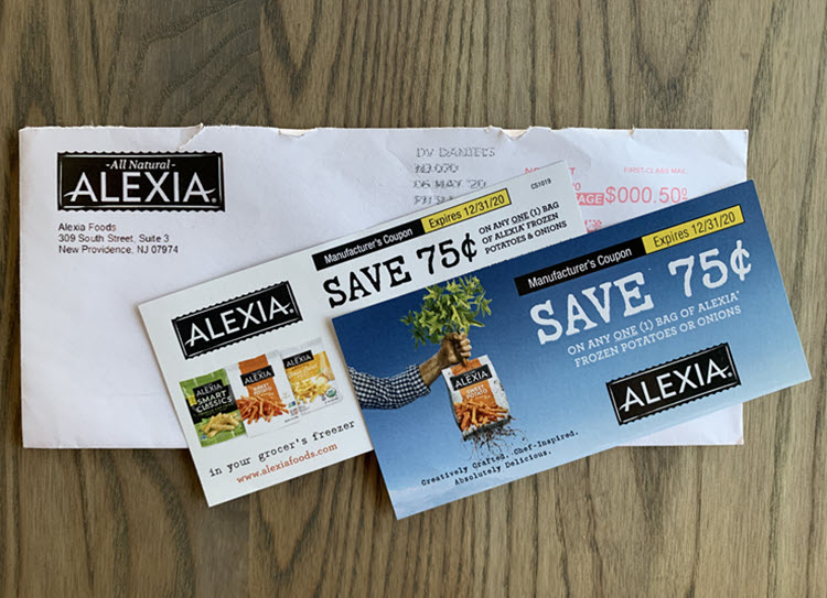Two coupons for 75 cents off alexia frozen foods on top of envelope and board.