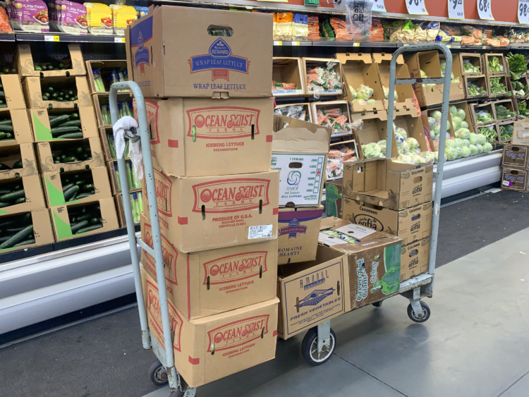 Cardboard produce boxes on a cart inside Winco.