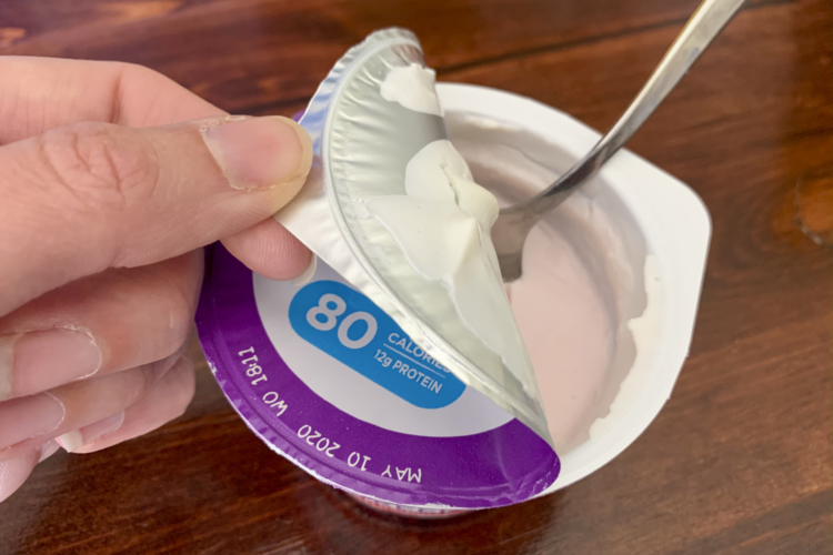 A spoon in a yogurt cup someone is pulling the metal lid off.