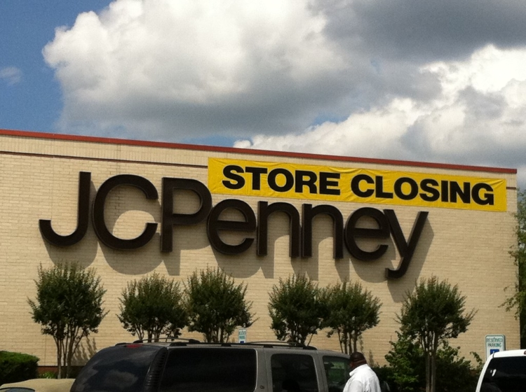 "close up of JCPenny store sign on the side of the building with a yellow banner above reading ""store closing""."