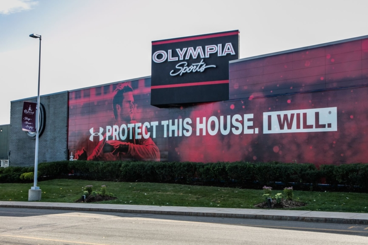 "Olympia Sports store with an under armour slogan displayed on the side of the building. ""Protect this house. I will."